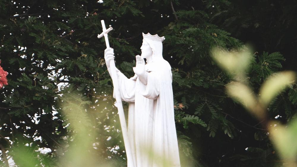 white angel statue near green leaf tree