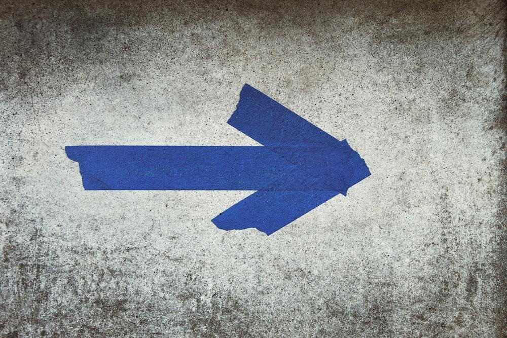 blue arrow sign on gray textile