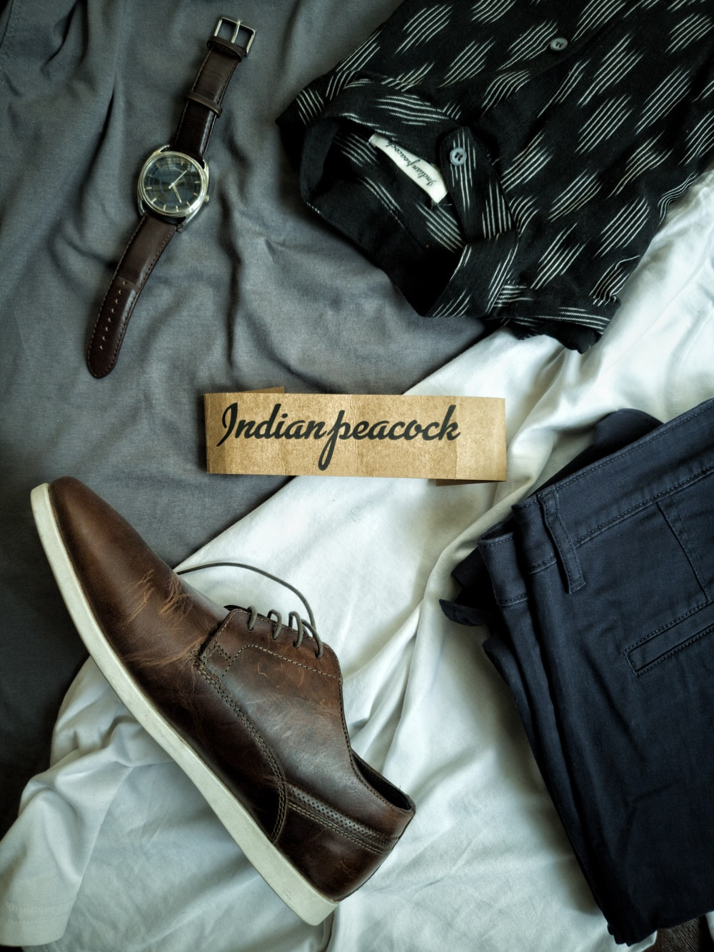 blue denim jeans beside brown leather strap silver round analog watch