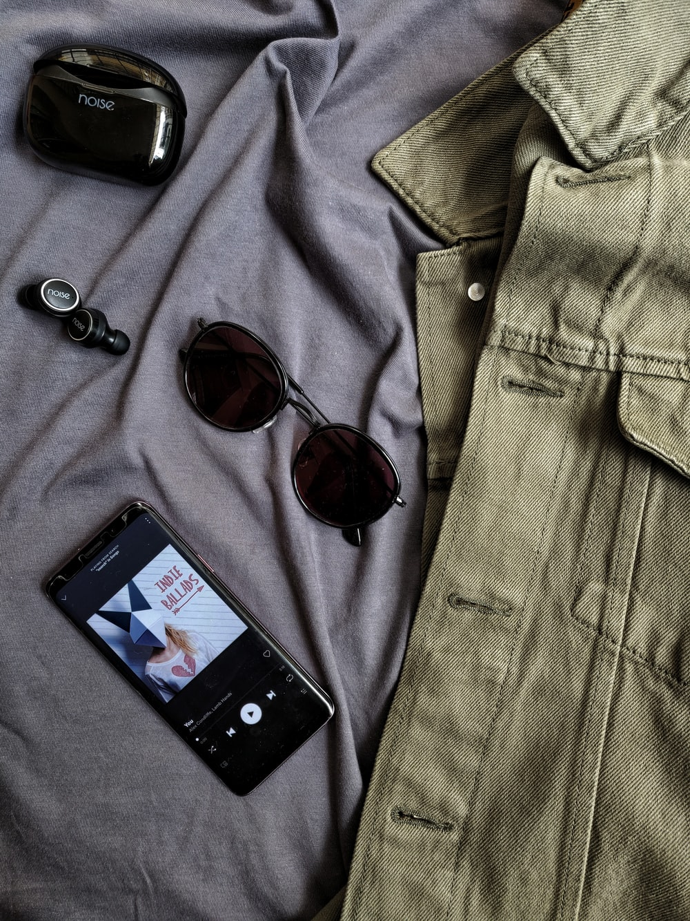 black iphone 4 beside brown framed sunglasses and gray denim button up shirt