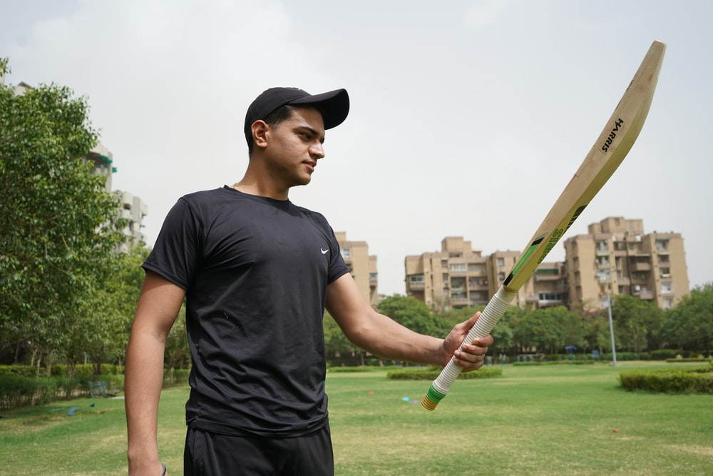 man in black crew neck t-shirt and black cap holding baseball bat