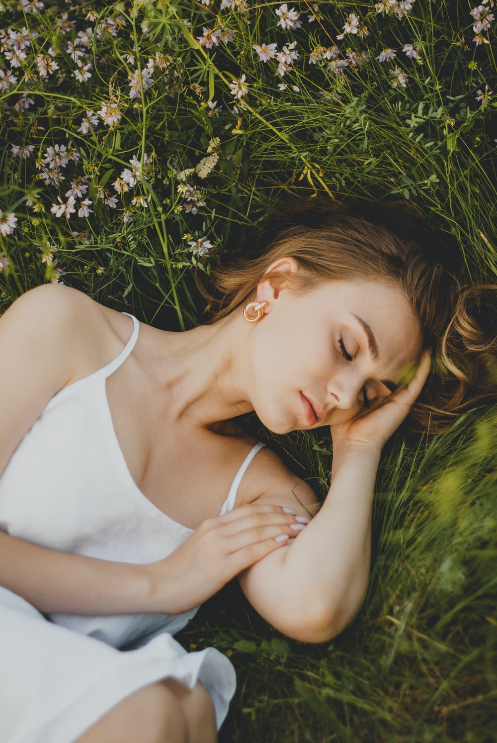 woman in white tank top lying on green grass during daytime