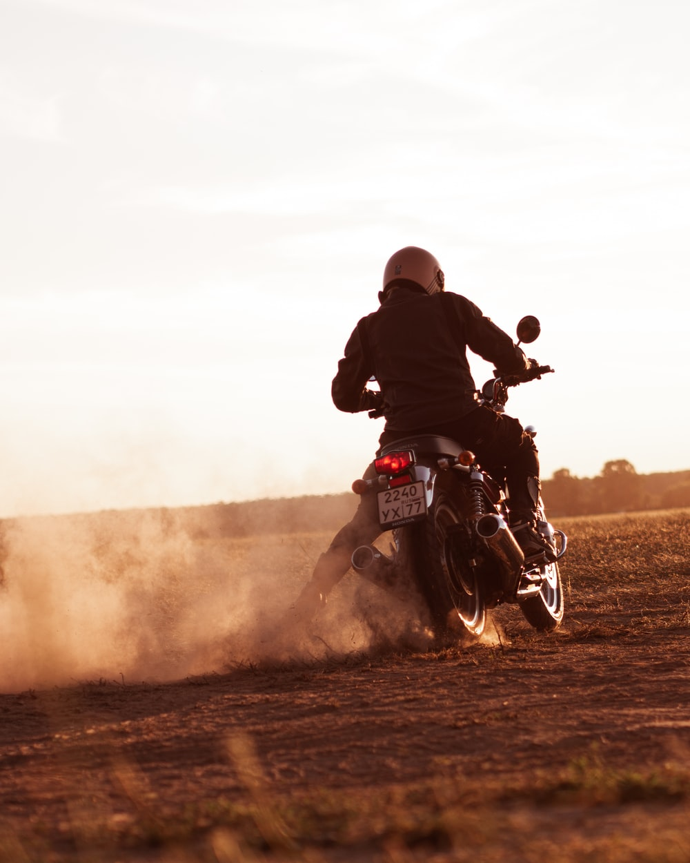 man riding on red and white dirt motorcycle during daytime