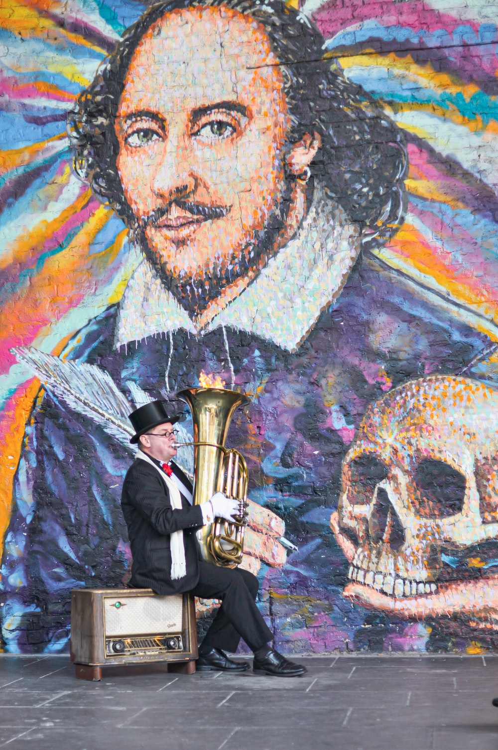 man in black suit jacket holding brass trumpet painting