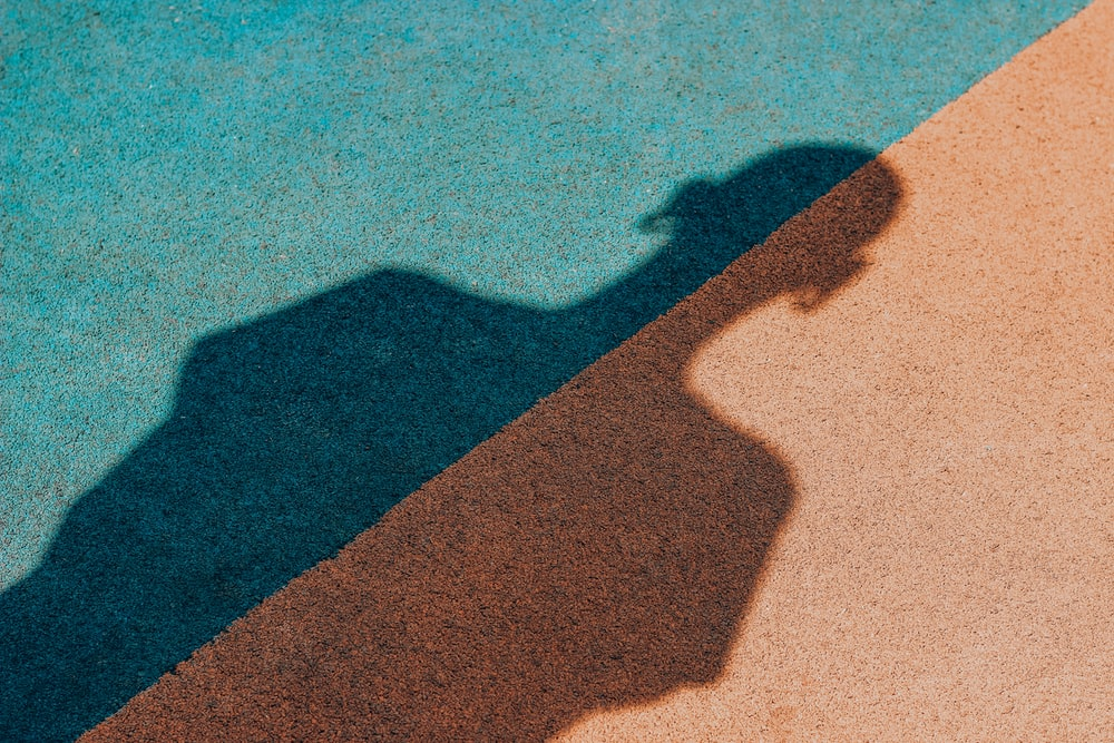 shadow of person on brown sand during daytime