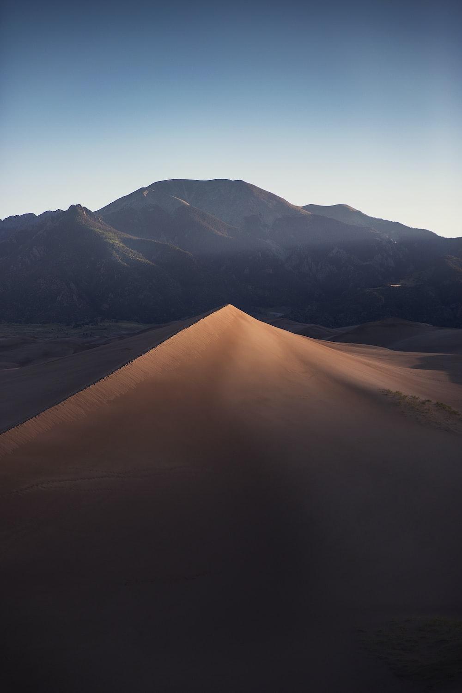 brown sand dunes near mountains during daytime