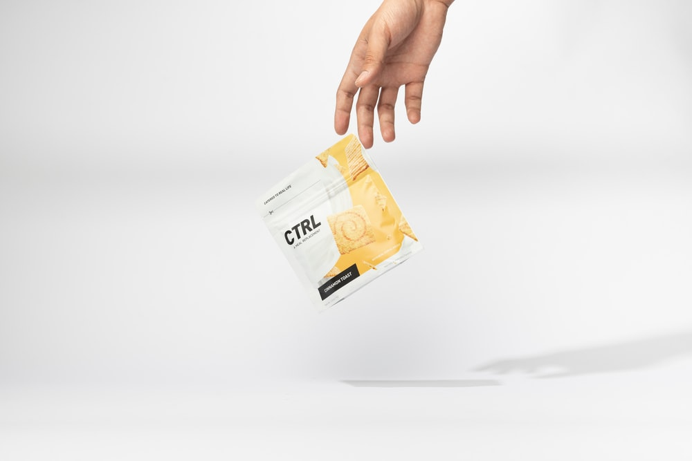 person holding orange and white plastic pack