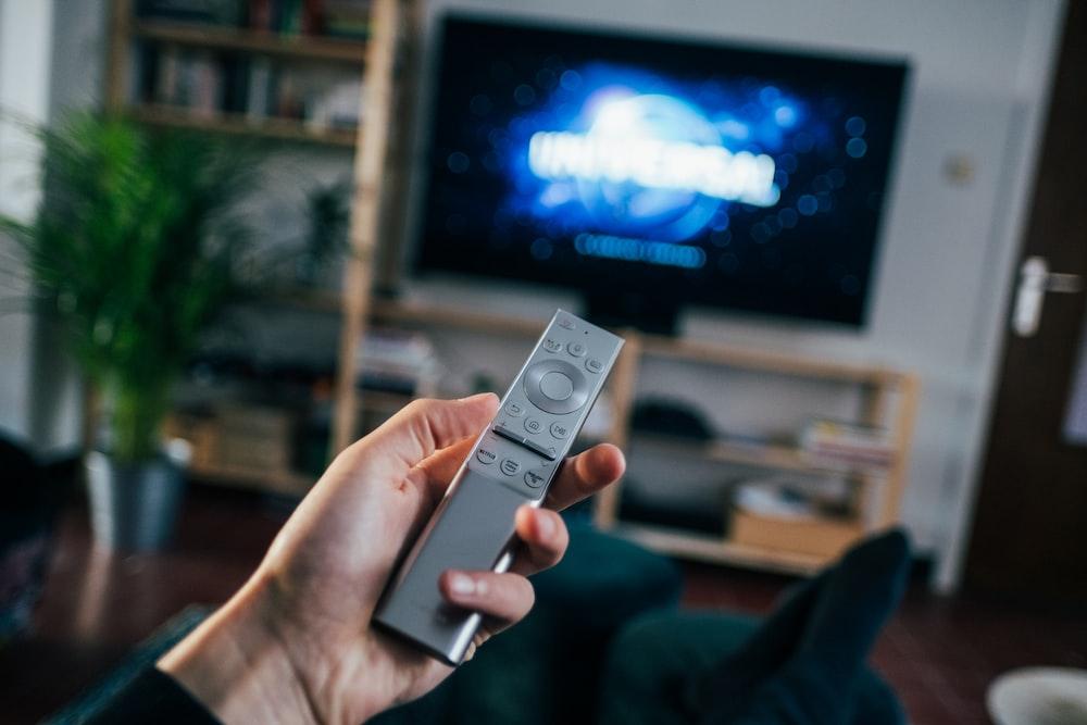 person holding gray remote control