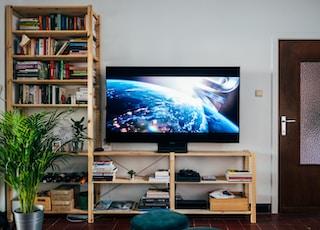 black flat screen tv turned on near brown wooden shelf