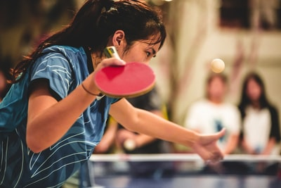 girl in blue and white striped shirt holding pink plastic cup table tennis teams background