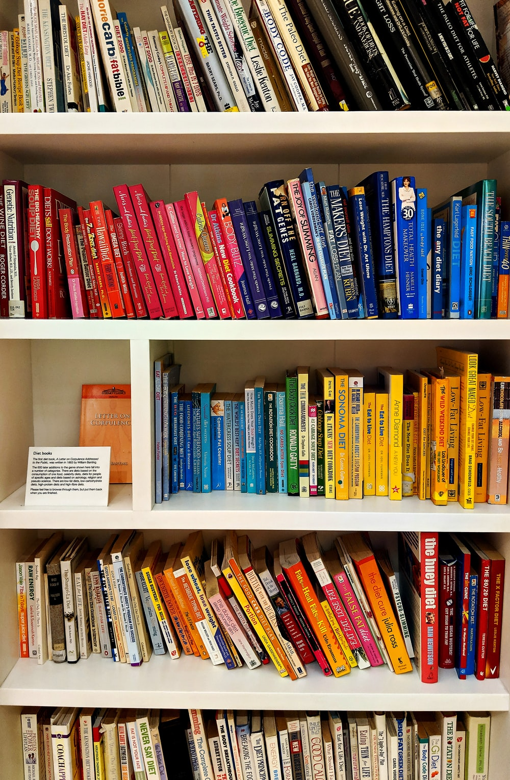 yellow blue red and green books on white wooden shelf