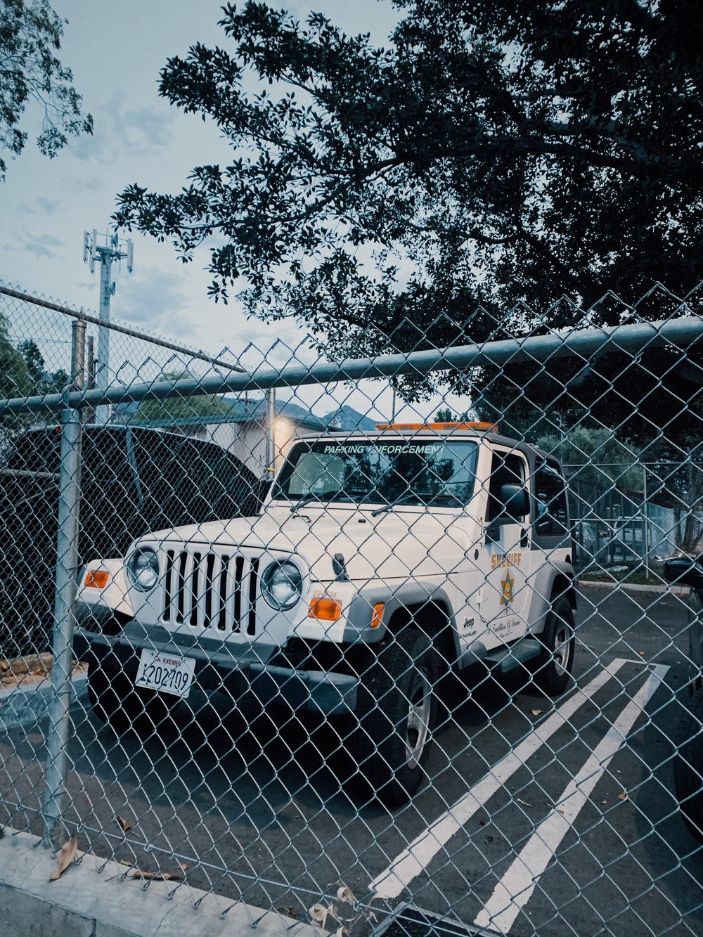 white and black jeep wrangler parked beside gray metal fence