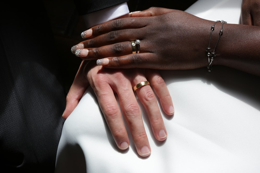 person wearing gold ring and gold ring