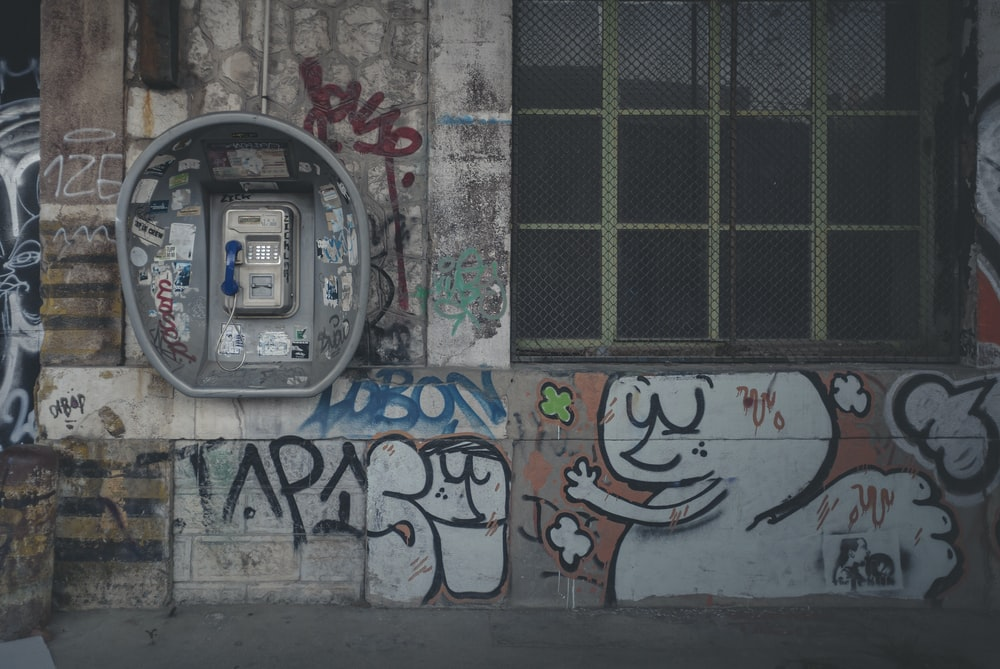 gray telephone booth beside white wall with graffiti