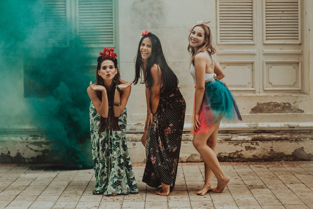 3 women in black and green dress standing on gray concrete floor