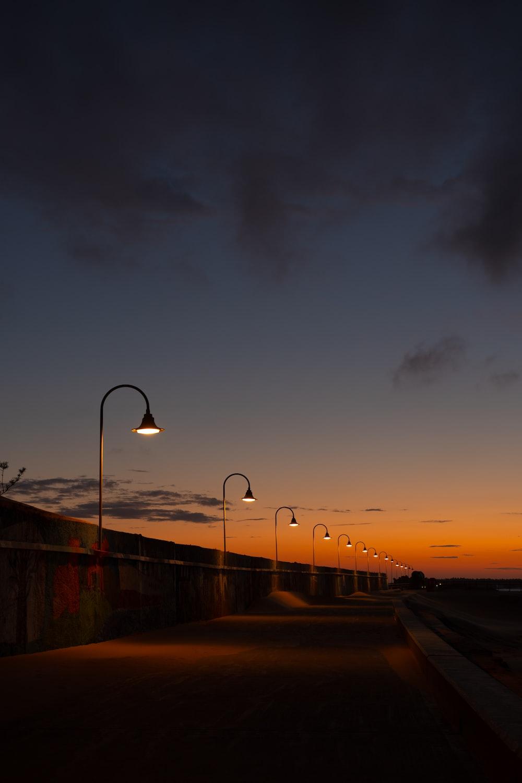 street light near body of water during sunset