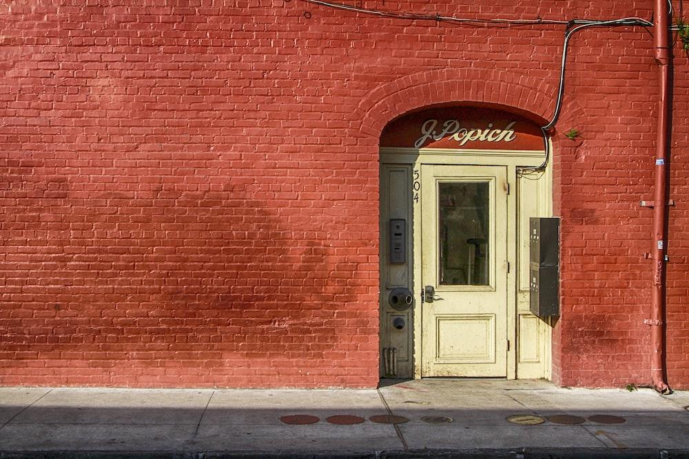 white wooden door beside red brick wall