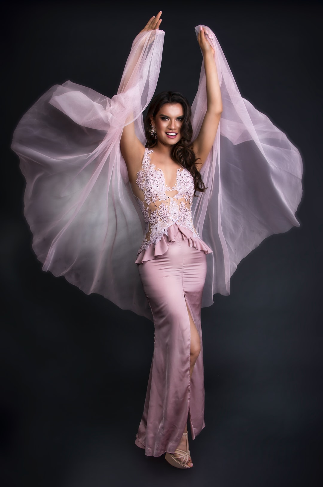 Woman in pink gala dress on black background