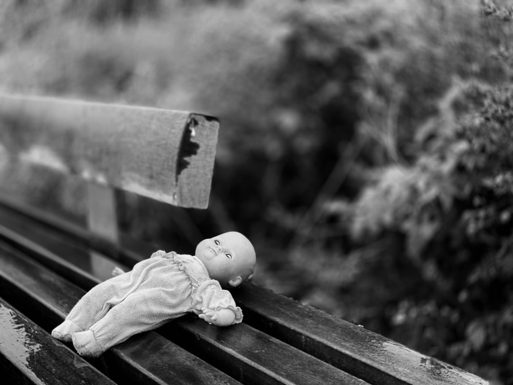 grayscale photo of baby doll on wooden bench
