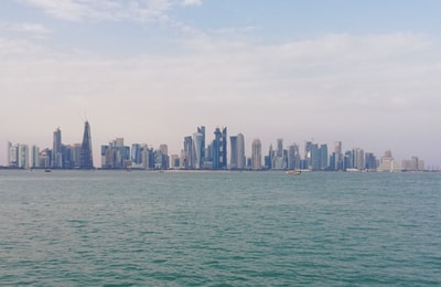 city skyline across body of water during daytime qatar teams background