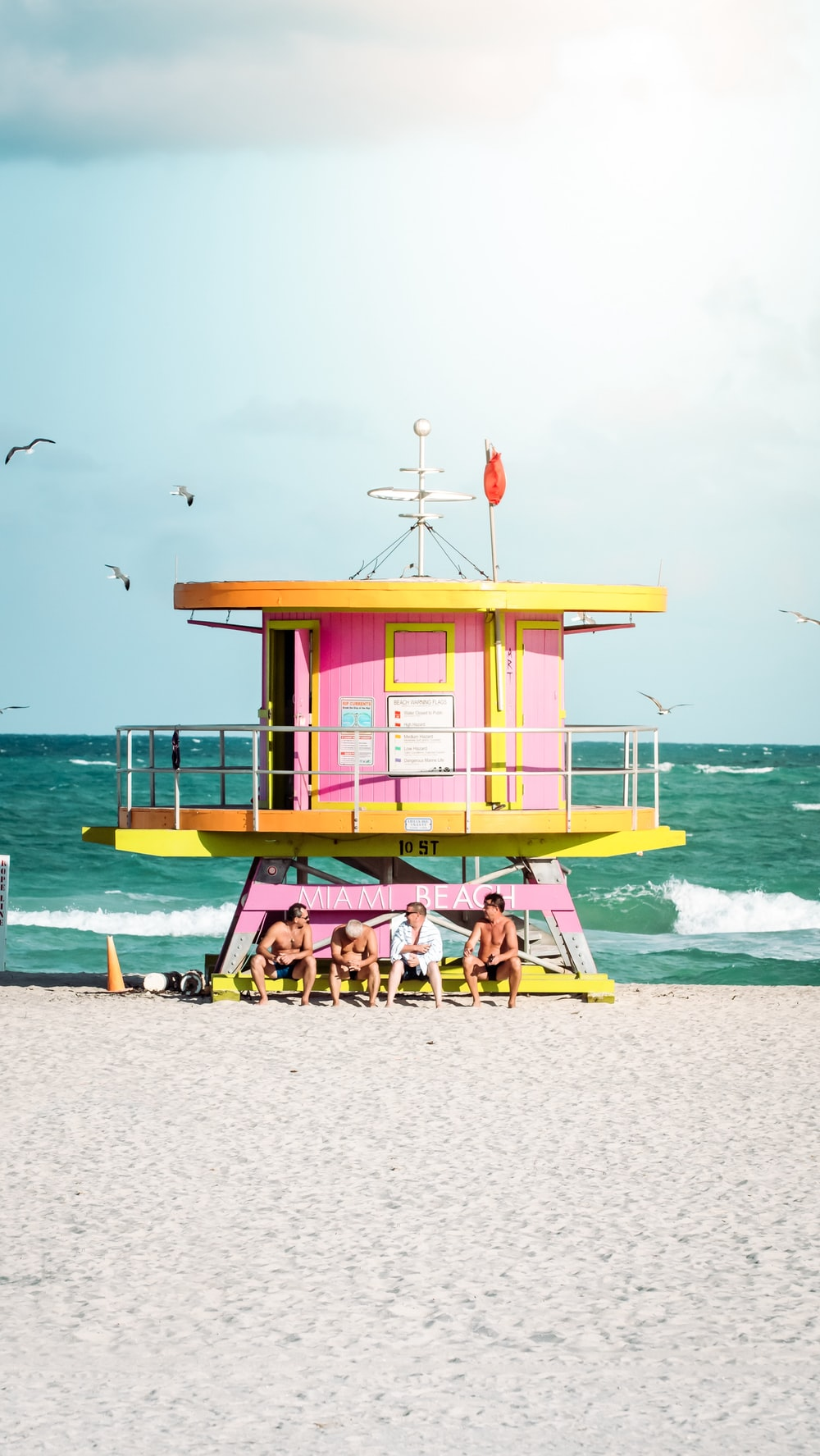 pink and yellow wooden lifeguard house on beach during daytime