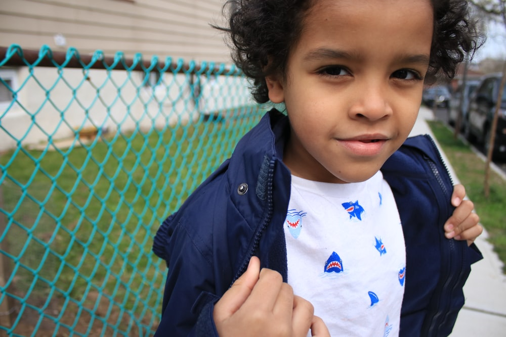 boy in blue and white crew neck shirt and black jacket