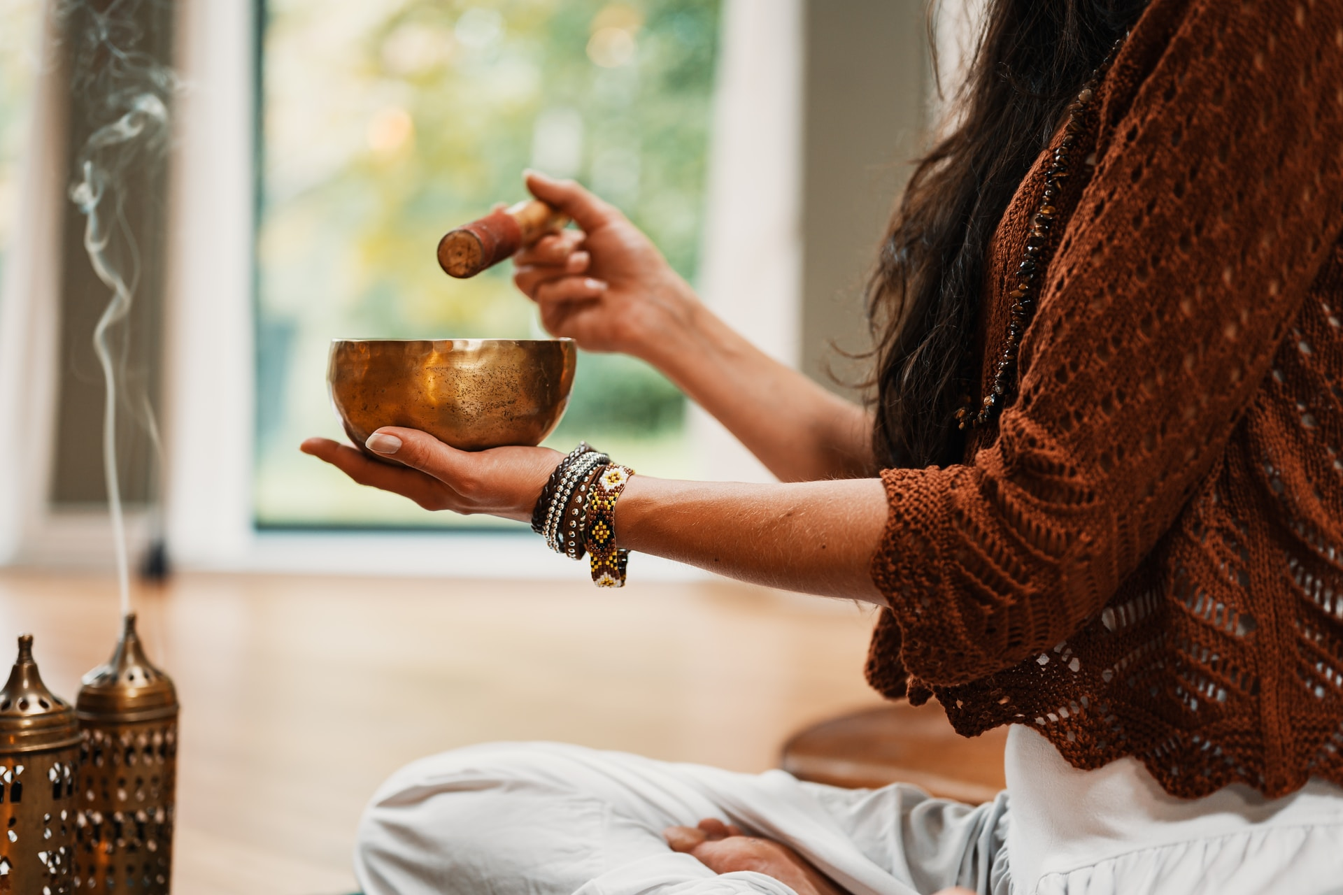woman in brown knit sweater holding brown ceramic cup