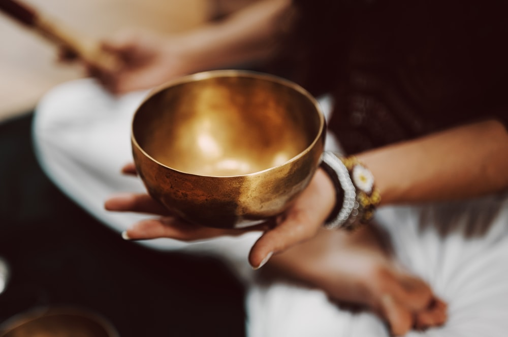 person holding brown ceramic bowl
