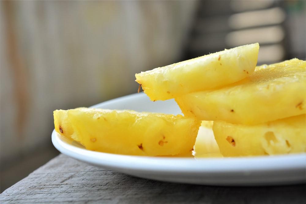 sliced yellow fruit on white ceramic plate