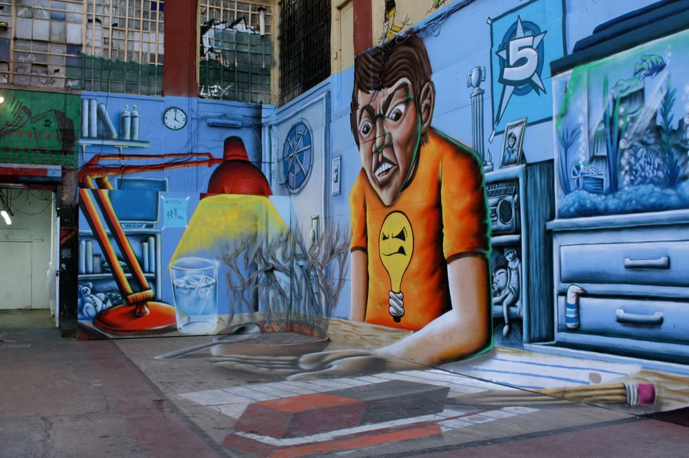 woman in yellow shirt standing beside wall with graffiti