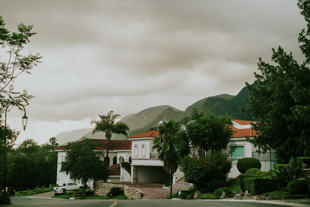 white and brown concrete house near green trees and mountain under white clouds during daytime
