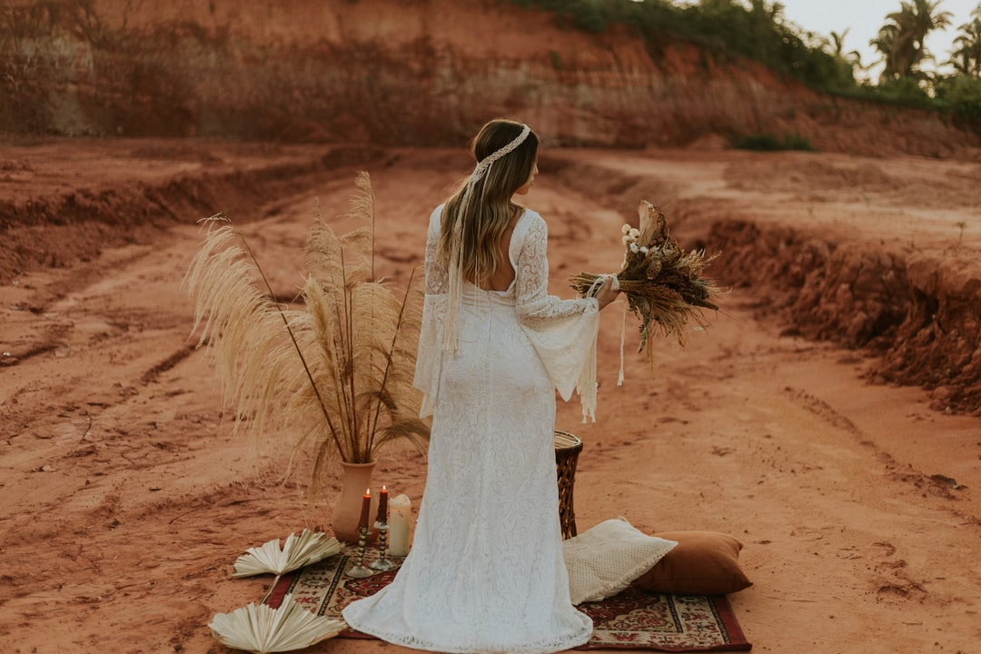 Woman In White Wedding Dress Sitting On Brown Sand During Daytime - unsplash