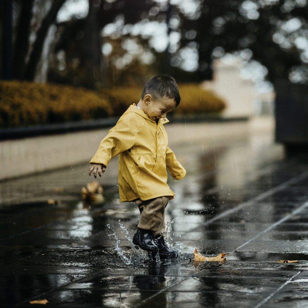 child in yellow hoodie walking on wet road during daytime
