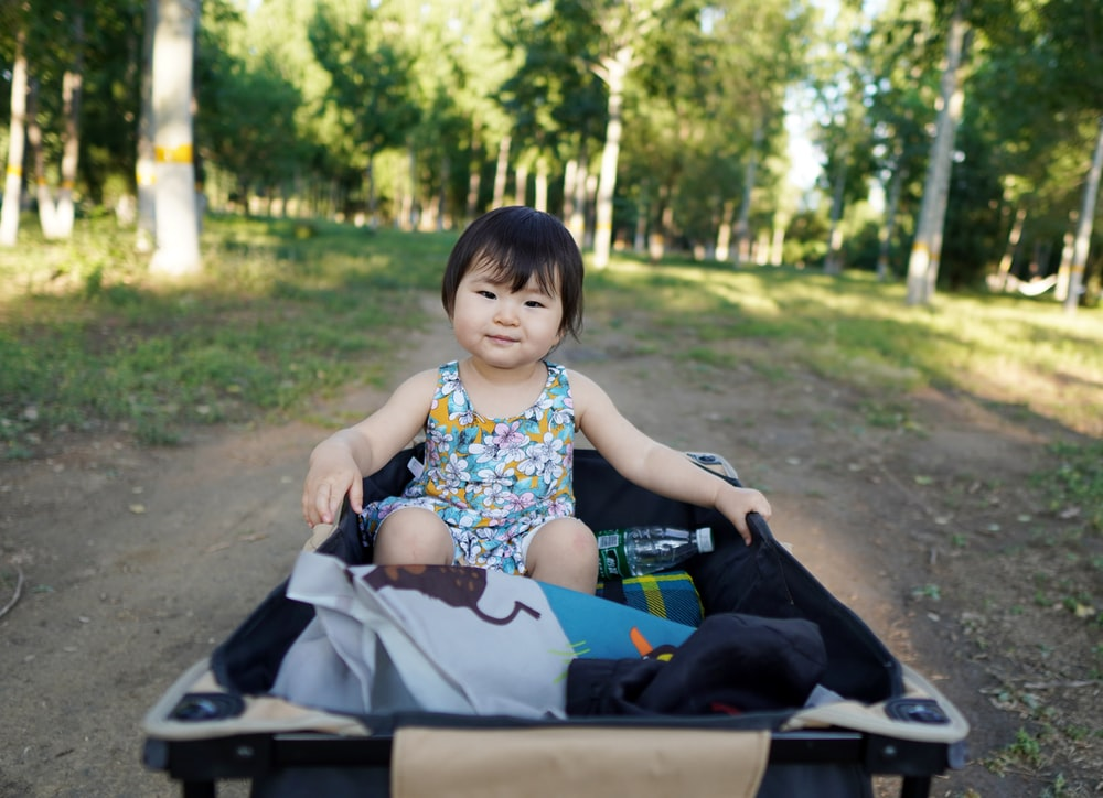 girl in blue and white floral sleeveless dress sitting on white and black stroller during daytime