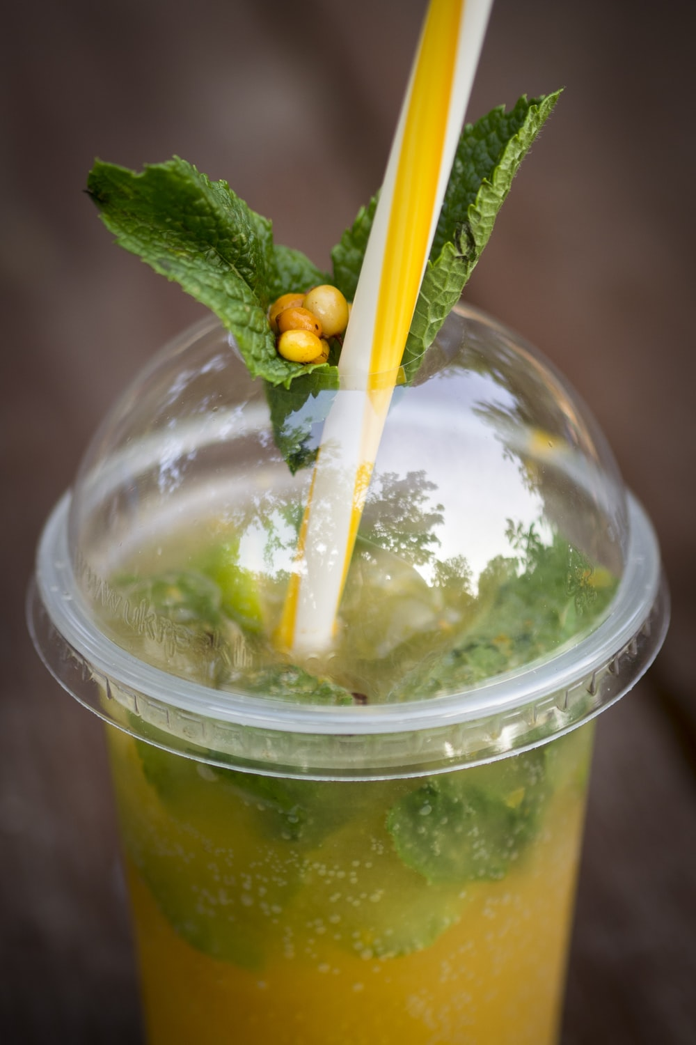clear plastic cup with yellow liquid and green leaf