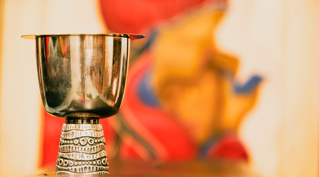Communion cup in front of a picture of Mary and Jesus, which is out of focus