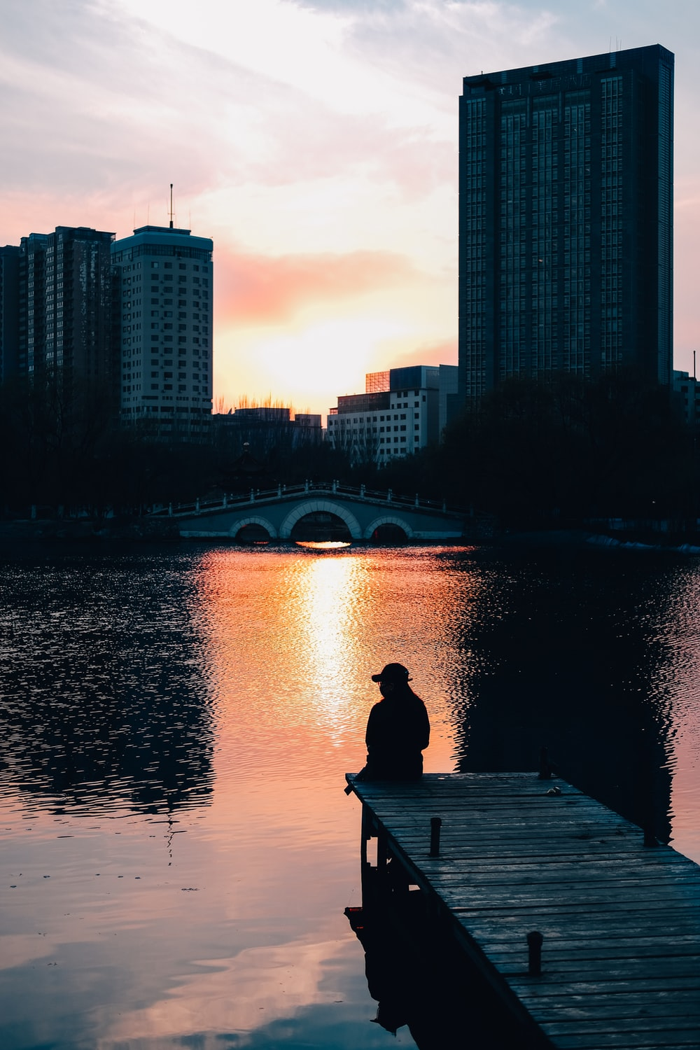man sitting on wooden dock near body of water during sunset