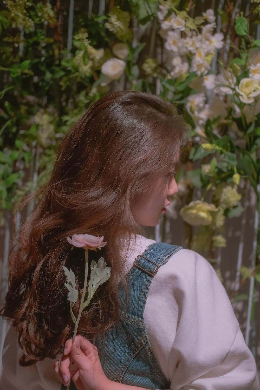 girl in white shirt holding white flower