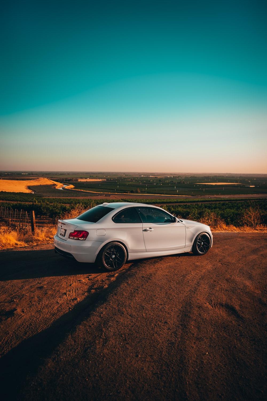 white sedan on brown dirt road during daytime
