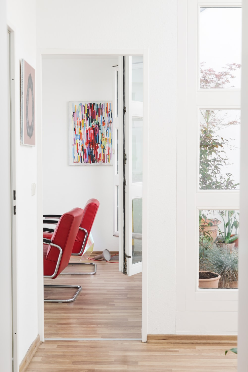 red and black armchair beside white wooden framed glass door
