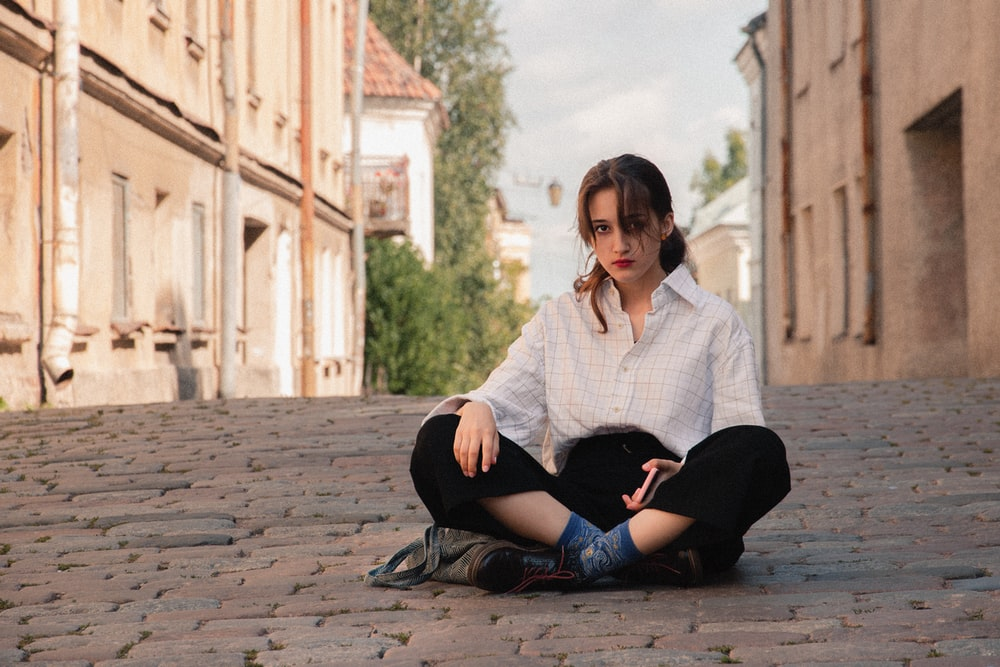 woman in white and black plaid dress shirt and black pants sitting on concrete floor during