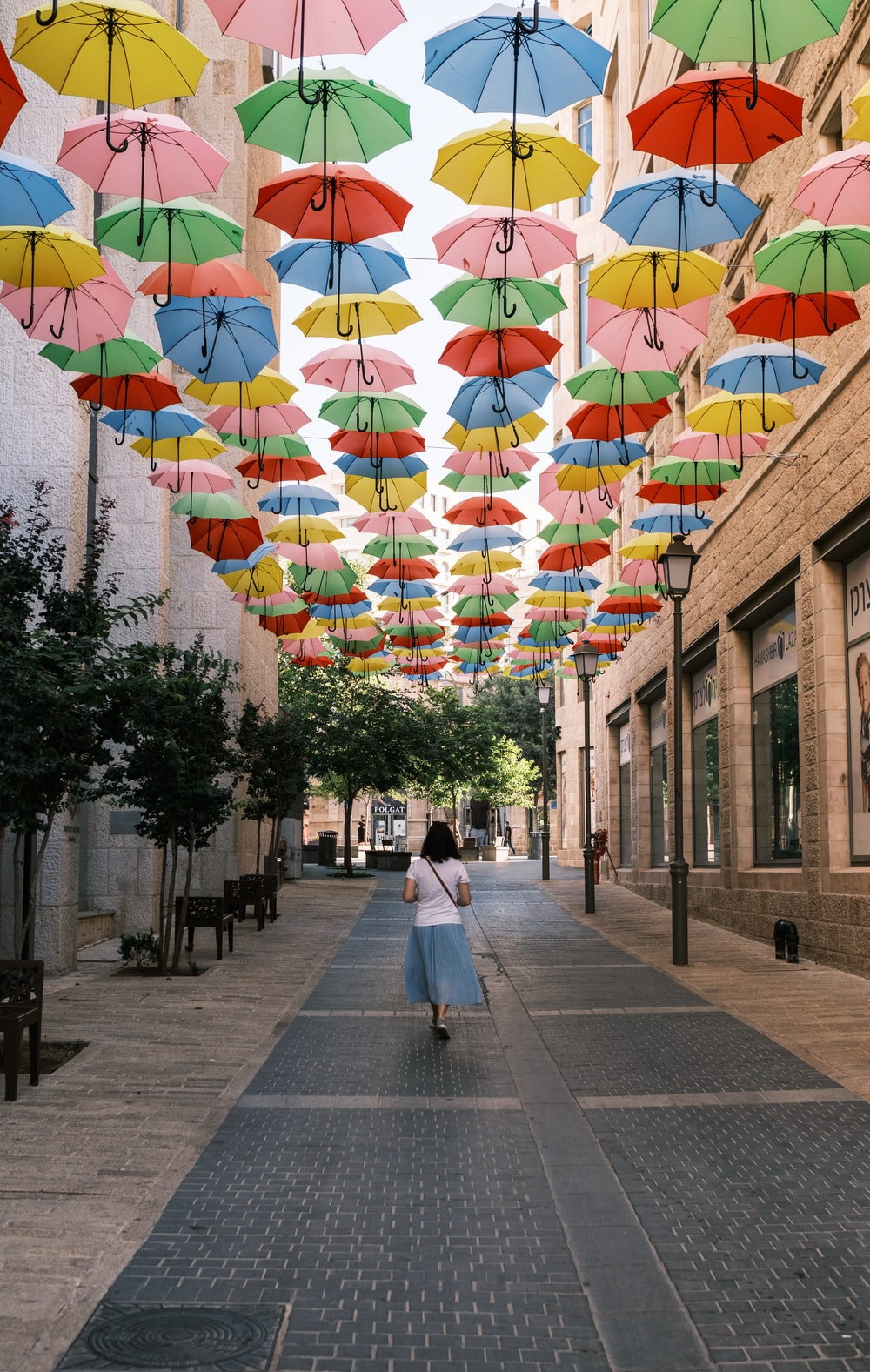 people walking on sidewalk with multi colored umbrellas on the street during daytime
