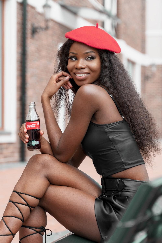 woman in black spaghetti strap dress holding coca cola bottle