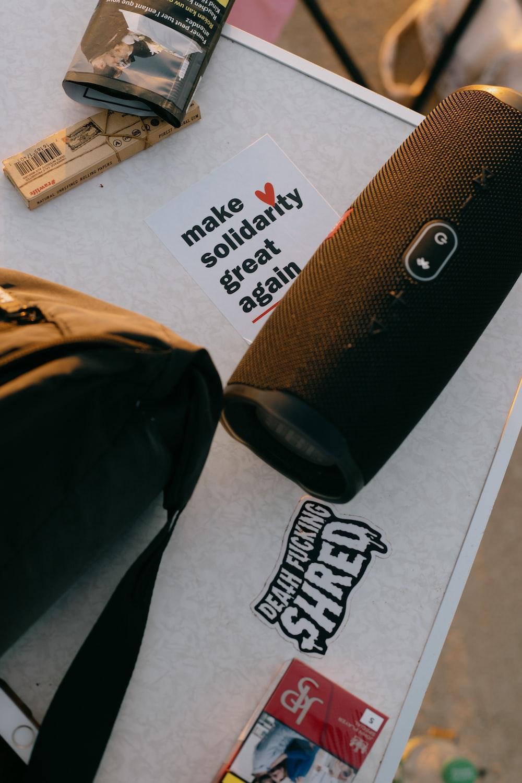 black jbl portable speaker on white printer paper