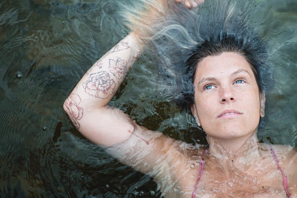 woman in pink bikini top floating on water