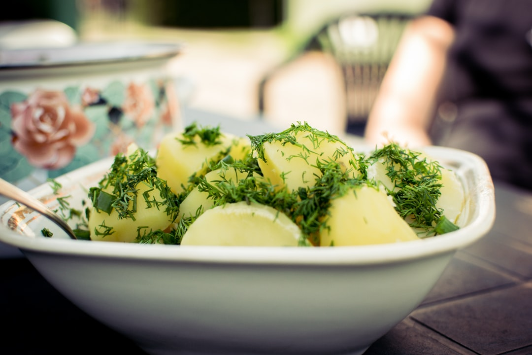 A bunch of boiled potatoes with dill on it in the summer morning.