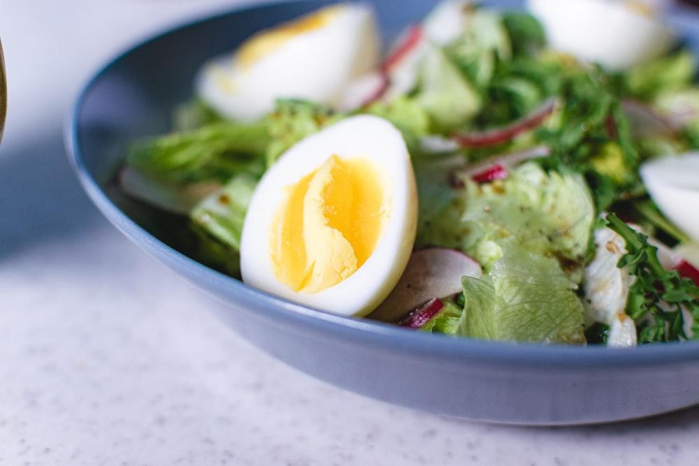 sliced tomato and green vegetable salad in white ceramic bowl