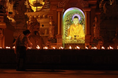 gold buddha statue in front of gold buddha statue religion teams background