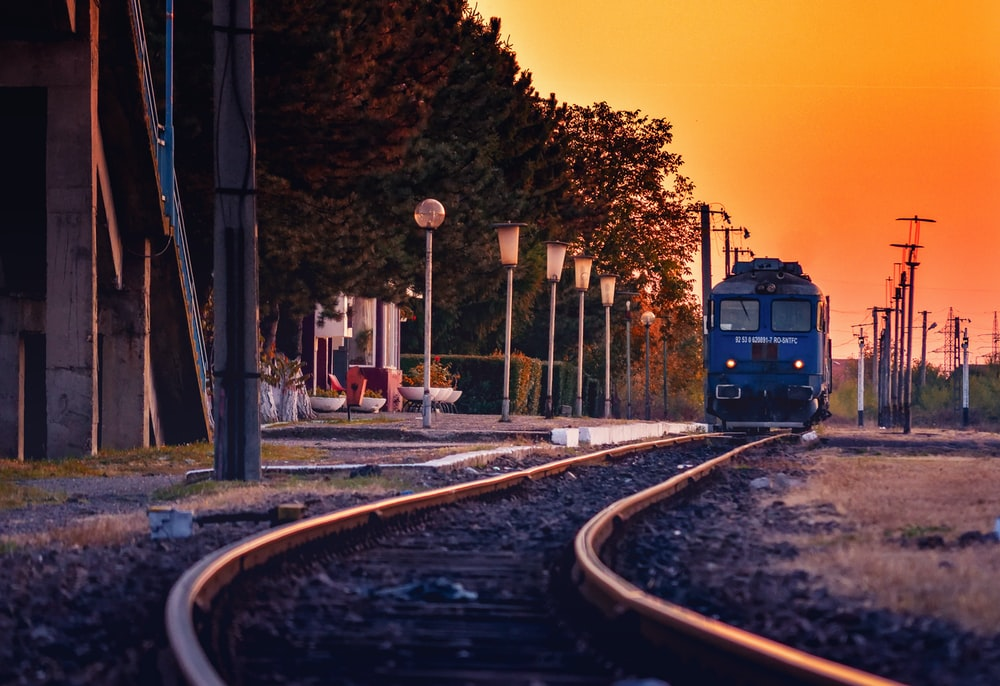 blue train on rail road during sunset