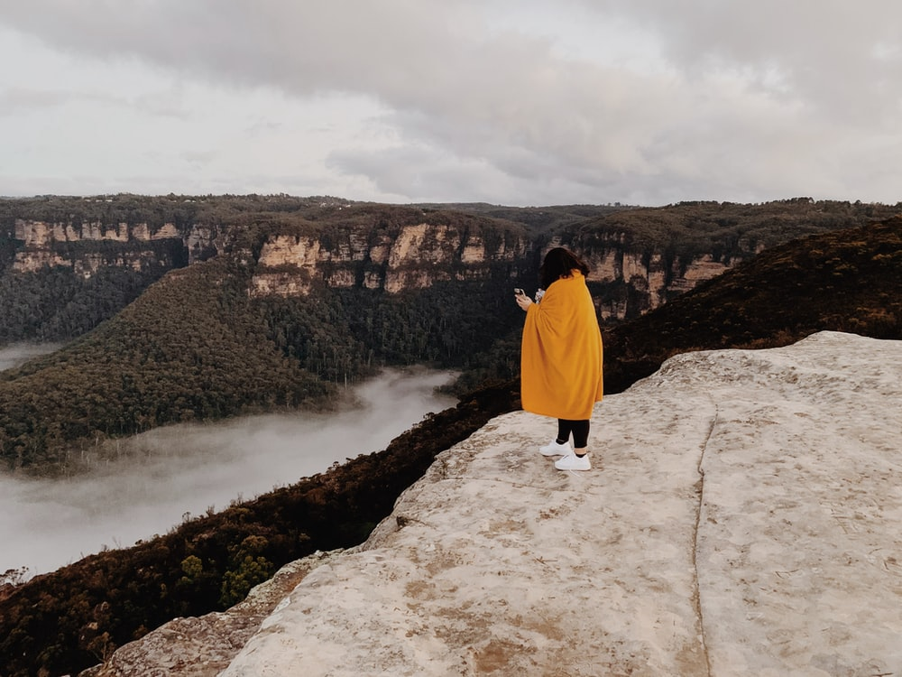 woman in yellow hoodie standing on rock formation near body of water during daytime